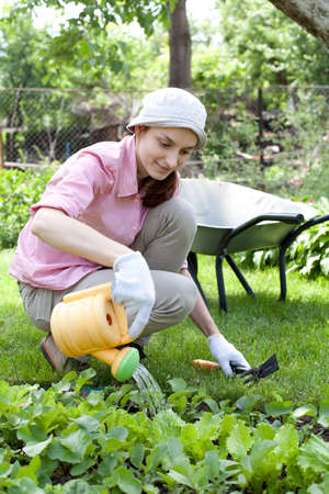 Young woman watering the garden bed photo