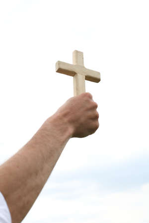 Hand with cross over the sky Stock Photo - 15536103