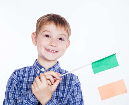 A little boy with Irish flag on the white background photo