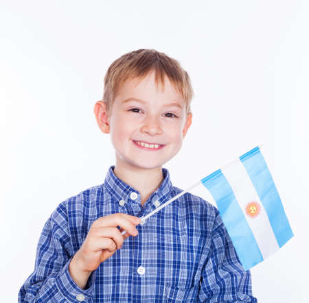 bandera argentina: Un niño pequeño con la bandera argentina en el fondo blanco Foto de archivo