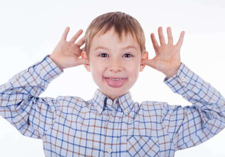 A small boy is  grimacing on the white background photo