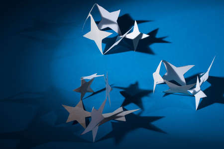 Paper christmas stars on the blue background . photo