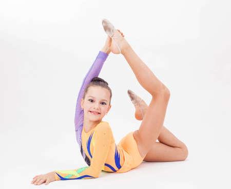 gymnastik: Vacker flexibel flicka gymnast över vit bakgrund Stockfoto