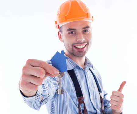 A builder man holding a key and a paper house. Stock Photo - 16657388