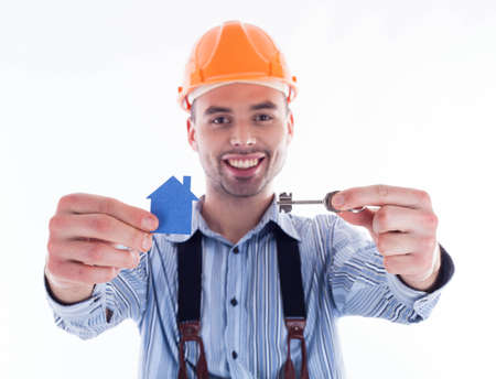 A builder man holding a key and a paper house. photo