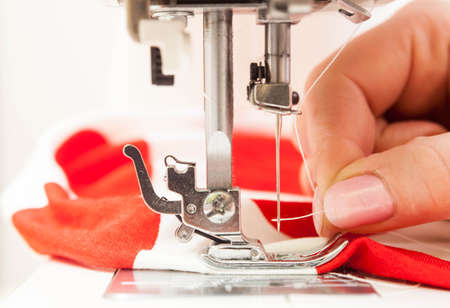 threading: A sewer threading a needle in the sewing machine.