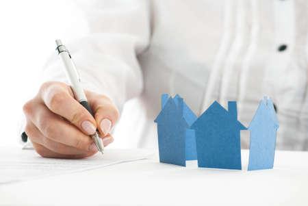 Hand Ausfüllen des Formulars mit Papier Häusern im Vordergrund.