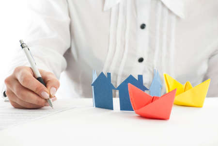 Hand filling out the form with paper houses and ships in foreground. photo