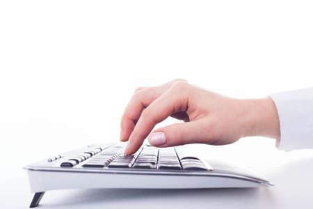 Female hand on the black keyboard on the white. photo