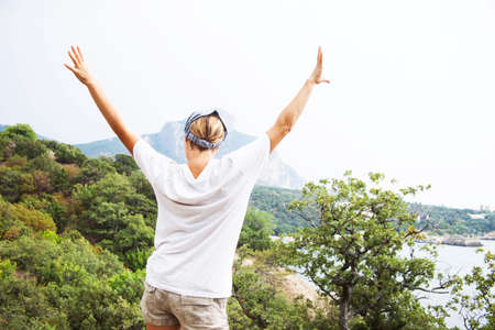 valley below: Young happy woman  standing on a rock with raised hands and looking to a valley below