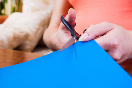 Woman's hand cutting blue paper with scissors photo