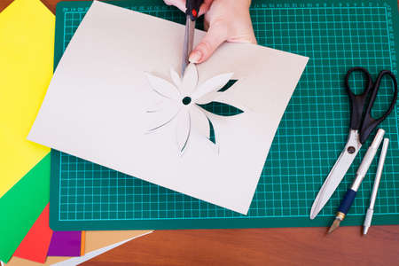 Womans hand cutting out flower from paper photo
