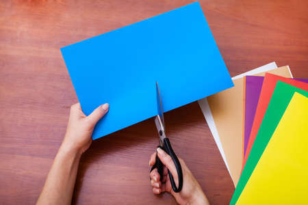 Womans hand cutting blue paper with scissors photo