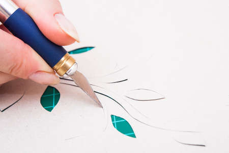 women's hand cutting flower from paper with spaper-knife photo