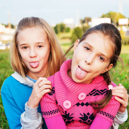 Little funny expressive girls with her tongue out photo