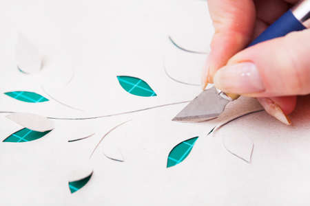 Woman's hand cutting out flower from paper photo