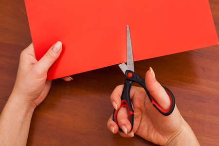 Womans hand is cutting paper with scissors photo