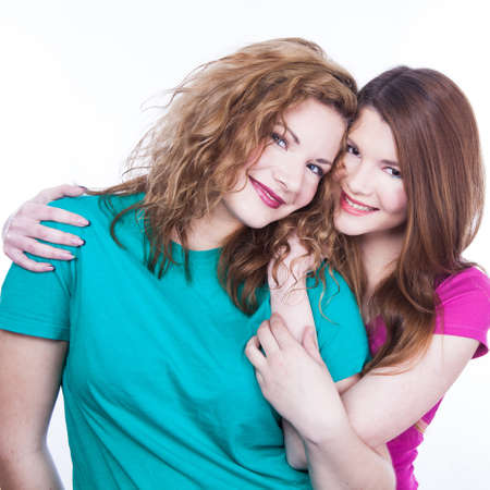 Two young women friends on the white background photo