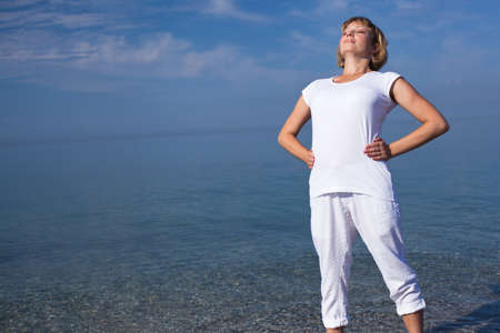 Yoga woman doing exercises at the seafront. photo
