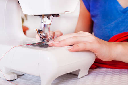 stitchwork: A tailor working on sewing machine from home Stock Photo