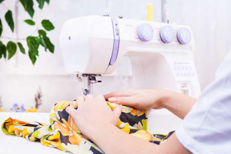 A tailor working on sewing machine from home Stock Photo
