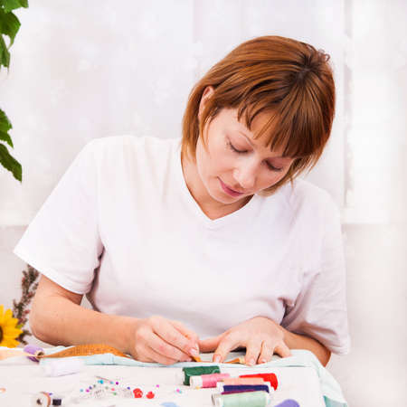 stitchwork: A tailor working measuring a garment from home Stock Photo
