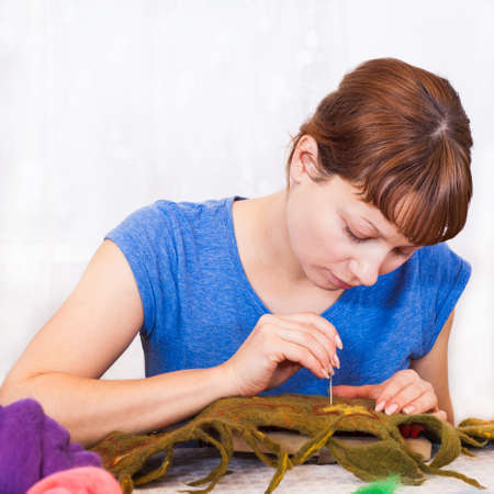 Felting activity, woman decorating a woolen scarf photo