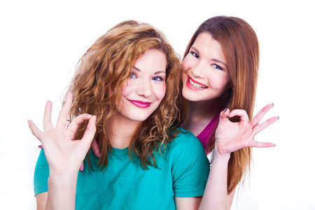 Young lighthearted girls shows Okay gesture,  on white background photo