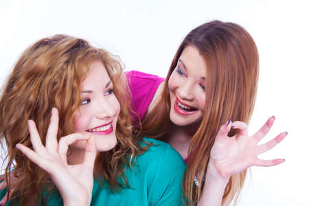 lighthearted: Young lighthearted girls shows Okay gesture,  on white background