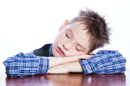 Sleeping boy on the table , isolated on white. photo