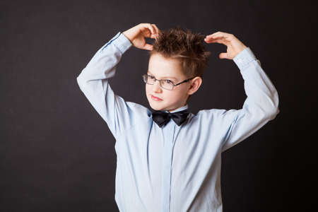 puzzlement: Boy  scratching his head thinking on black background Stock Photo