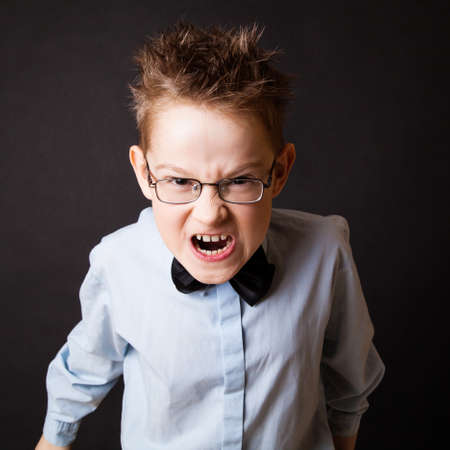 playful behaviour: Little boy making angry face against the black background