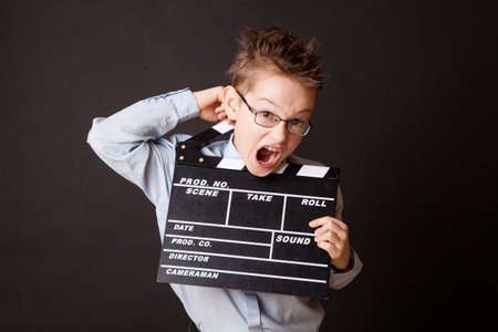 Little boy holding clapper board in hands. Cinema concept. photo