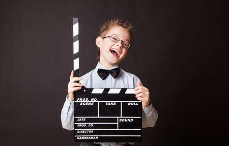 Kleiner Junge mit Filmklappe in der Hand. Cinema-Konzept. Lizenzfreie Bilder