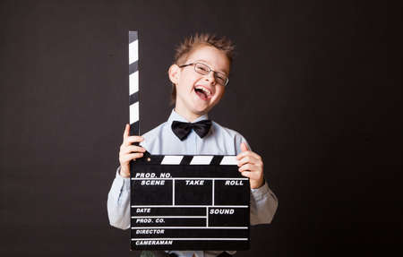 Little boy holding clapper board in hands. Cinema concept.