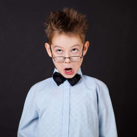 dance preteen: Little boy with funny face on black background Stock Photo