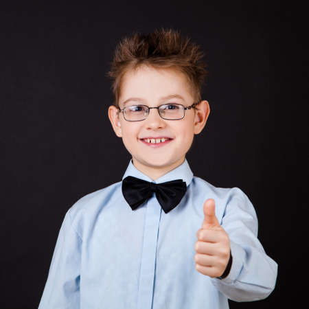 little boy smiling andshowing ok sign over the black photo