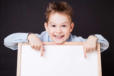 Portrait of cheerful boy pointing on white banner on the black background photo