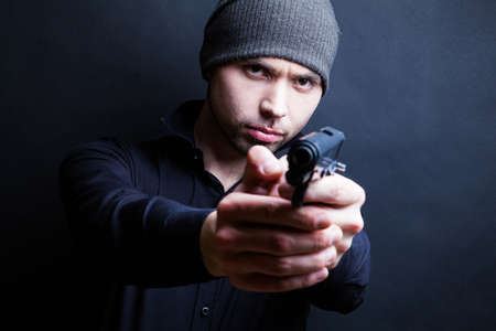Portrait of a man holding gun against a black background photo
