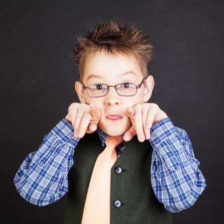 grimacing: Young funny boy grimacing over the black Stock Photo