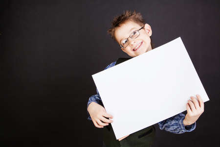 nine years old: Cute boy with white empty banner against the black Stock Photo