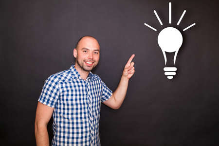 Young happy man pointing  his finger to the bulb photo