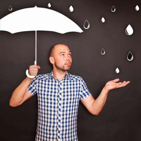 Man holding drawn umbrella in the rain photo