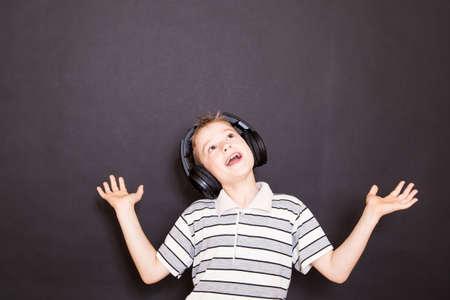 niño cantando: El muchacho juguetón escuchar música en los auriculares