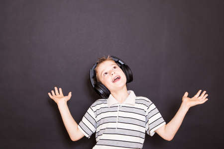 child singing: The playful boy  listening to music in headphones Stock Photo