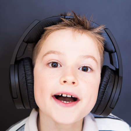The playful boy  listening to music in headphones photo