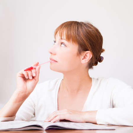 Young  beautiful woman doing crosswords in room photo