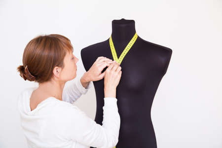 Woman tailor making measurements on the mannequin photo