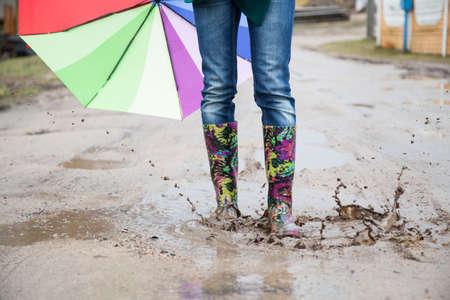botas de lluvia: Mujer con botas de lluvia salta Foto de archivo