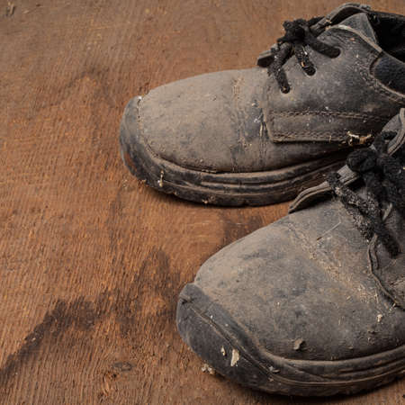 dirty feet: Grunge old boots on  the wood background